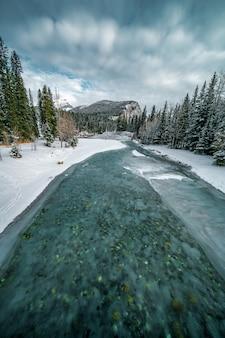 Verticaal schot van een bevroren turkooise rivier in een gebied dat met sneeuw naast een bos wordt behandeld