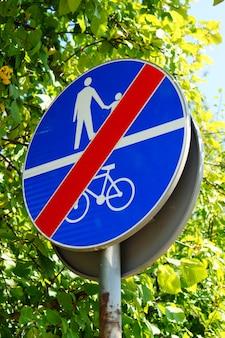 Verticaal schot van een blauw bord dat de toegang van mensen en fietsen verbiedt