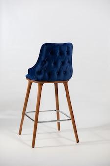 Verticaal schot van een blauwe stoel die uit houten benen wordt samengesteld