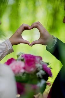 Verticaal schot van een bruid en een bruidegom die een hart met hun handen houden