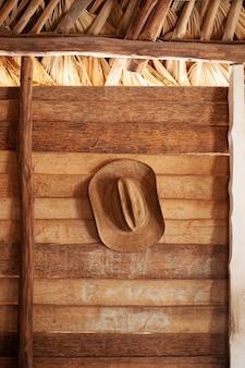 Verticaal schot van een bruine hoed die op een houten muur hangt