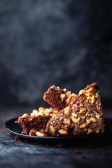 Verticaal schot van een chocoladecake met okkernoten in een zwarte plaat met vaag