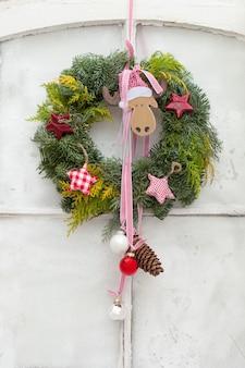 Verticaal schot van een decoratieve kroon van kerstmis met ornamenten die op een witte deur hangen