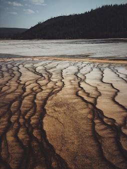 Verticaal schot van een droog zout meer met een beboste berg