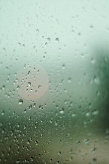 Verticaal schot van een glas met regendruppels die de perfecte herfst vormen