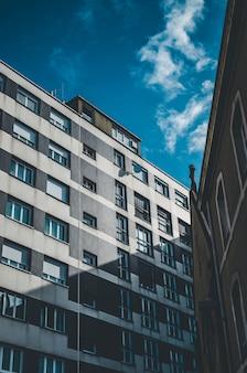 Verticaal schot van een grijs en wit gebouw met vensters onder een blauwe hemel