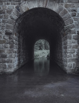 Verticaal schot van een grijze steenwatertunnel