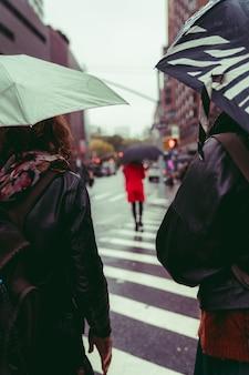 Verticaal schot van een groep mensen die onder de regen op straat lopen