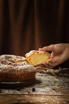 Verticaal schot van een hand die een stuk van een heerlijk biscuitgebak met poedersuiker neemt