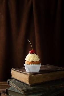 Verticaal schot van een heerlijke cupcake met room en kers op bovenkant op boeken