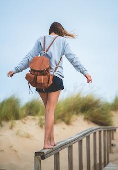 Verticaal schot van een jong meisje dat op een houten leuning loopt op het strand in het zonlicht