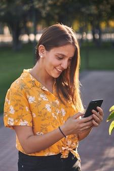 Verticaal schot van een jong meisje in een geel overhemd die haar telefoon bekijken en glimlachen