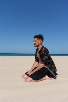Verticaal schot van een jonge man zittend op het zand op het strand