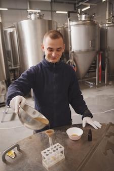 Verticaal schot van een jonge mannelijke brouwer die kwaliteitstests uitvoert bij microbrouwerij