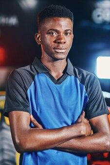 Verticaal schot van een jonge zelfverzekerde afrikaanse man, mannelijke cybersport-gamer die zijn armen gekruist houdt en