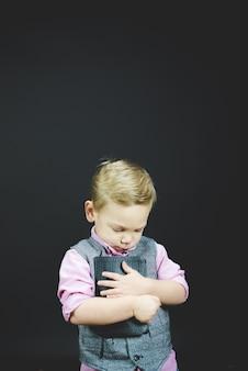 Verticaal schot van een kind dat de bijbel tegen zijn borst houdt