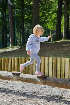 Verticaal schot van een klein meisje dat op een houten buis in de speelplaats loopt
