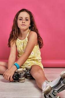 Verticaal schot van een klein meisje in rolschaatsen dat op de grond zit