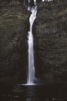 Verticaal schot van een kleine waterval in het centrum van de bemoste rotsen