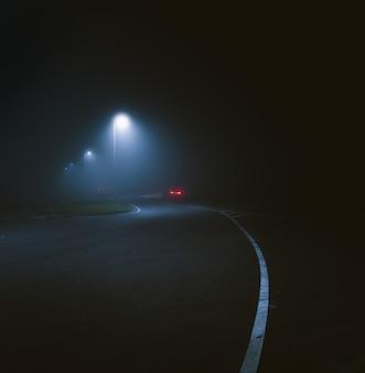Verticaal schot van een lantaarnpaal bij de straat, vastgelegd tijdens de nacht