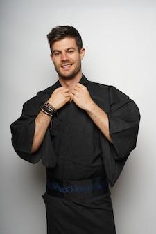 Verticaal schot van een man die een kimono in japanse stijl draagt en glimlacht