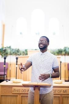Verticaal schot van een mannetje dat de bijbel leest dichtbij de tribune in de kerk