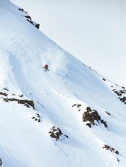 Verticaal schot van een mannetje dat op de berg ski? t die met sneeuw in de winter wordt behandeld