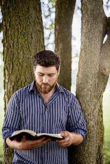 Verticaal schot van een mannetje leunde tegen een boom terwijl het lezen van de bijbel