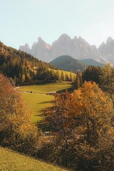 Verticaal schot van een mooie dorpsweg op een heuvel die door bergen wordt omringd