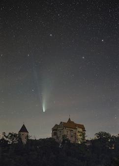 Verticaal schot van een neowise-komeet die over het pernstejn-kasteel in de tsjechische republiek vliegt