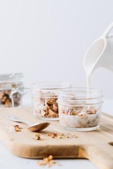 Verticaal schot van een oatenontbijt met melk die op wit wordt geïsoleerd