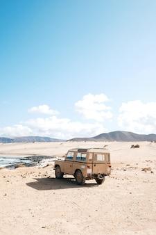 Verticaal schot van een off-road auto die zich in een woestijn bevindt