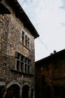 Verticaal schot van een oud baksteengebouw onder de mooie bewolkte hemel