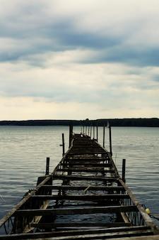 Verticaal schot van een oude half-gebroken pier met bewolkte luchten in miedwie, stargard, polen.