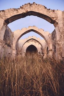 Verticaal schot van een oude oude ruïne met een gewelfd plafond in een droog grasveld onder een blauwe hemel