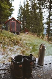 Verticaal schot van een paar laarzen en een kolf dichtbij een houten huisje in het bos in noorwegen