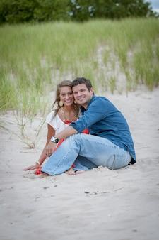 Verticaal schot van een paarzitting op een zandige kust terwijl het glimlachen