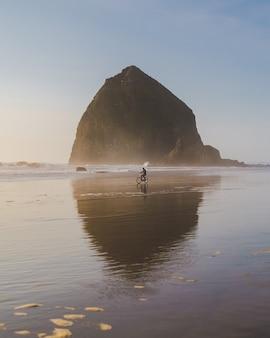 Verticaal schot van een persoon die een fiets aan de kust met een grote rots in de verte berijdt