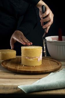 Verticaal schot van een persoon die een kleine vanillecake voorbereidt