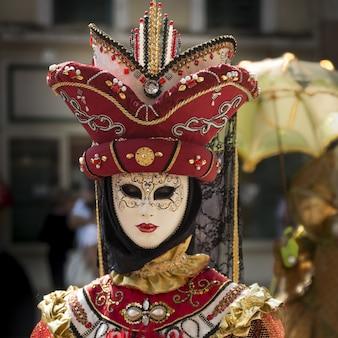 Verticaal schot van een persoon die een venetiaans carnaval-masker en kleding draagt
