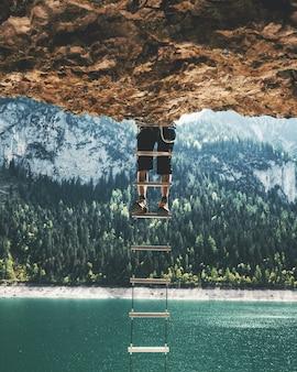 Verticaal schot van een persoon die op een ladder beklimt die van een klip hangt