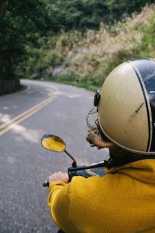 Verticaal schot van een persoon met een helm die op een motorfiets berijdt