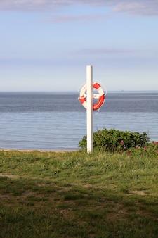 Verticaal schot van een reddingsboei die op een pijler hangt in oesterstrand, fredericia, denemarken
