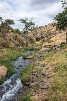 Verticaal schot van een rivier die door rotsen en kiezelstenen wordt omringd die in kenia, nairobi, samburu wordt gevangen