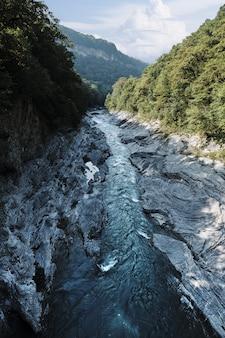 Verticaal schot van een rivier in het midden van klippen met bomen onder een blauwe hemel overdag