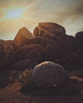 Verticaal schot van een rots met de zon die in de hemel glanst