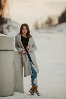 Verticaal schot van een sexy vrouw met een grijze jas leunend op de muur in een besneeuwd park
