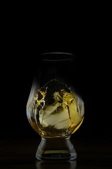 Verticaal schot van een spattende gouden gekleurde vloeistof in een geïsoleerd glas