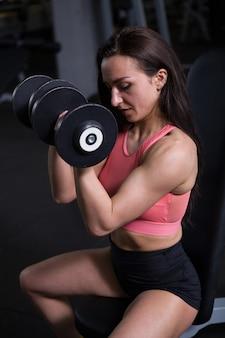 Verticaal schot van een sterke vrouwelijke atleet met gespierd lichaam die gewichten heft in de sportschool