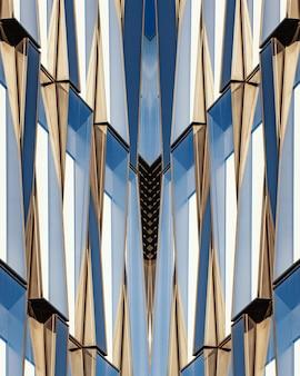 Verticaal schot van een symmetrisch blauw glas en een betonnen gebouw